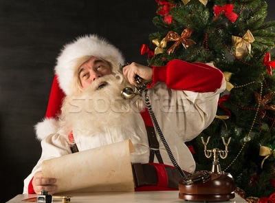 3566115_stock-photo-santa-claus-calling-with-vintage-phone-while-reading-an-old-roll