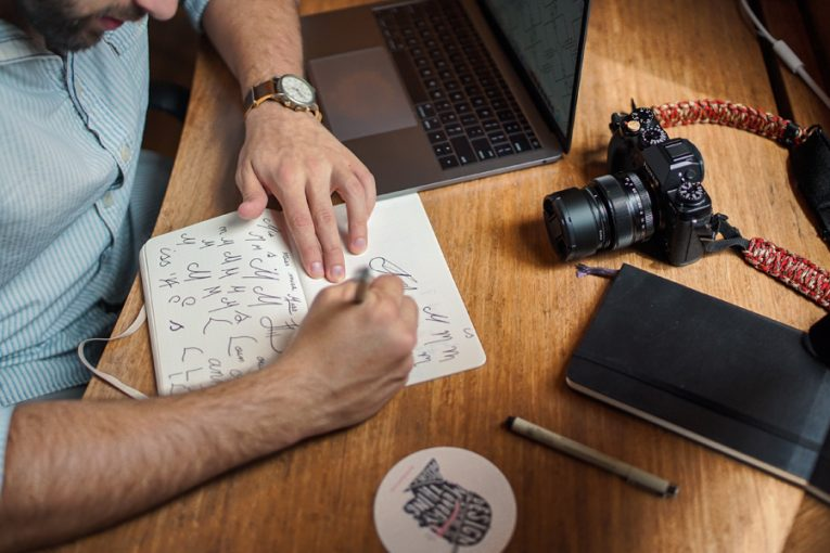Graphics designer writing on a notebook
